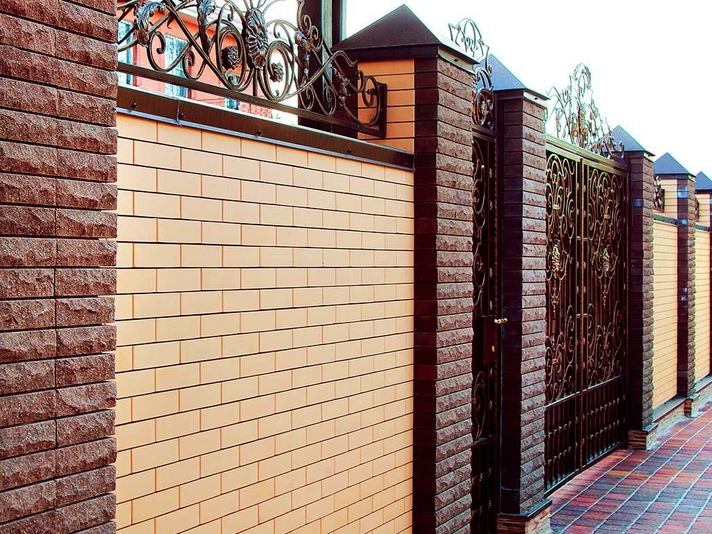 Кирпичный забор со столбами из дикого камня